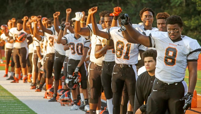 While a few players kneeled, most of the Withrow High School football team stood with fists raised during the national anthem before a game in 2016 at Anderson High School.
