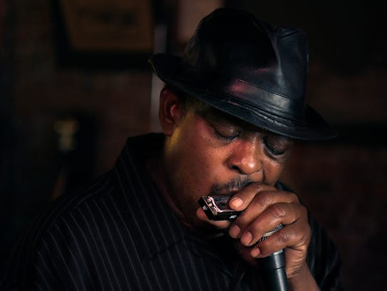 Vince Johnson plays the harmonica with his band, the