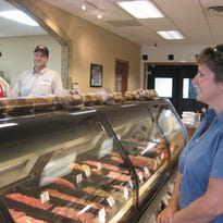In this Post-Crescent Media file photo, Employee Alec Schwalenberg (left) assists customer Sara Wiegert of Hollandtown with an order at Haen Meat Packing in Kaukauna as co-owner Tim Haen looks on.