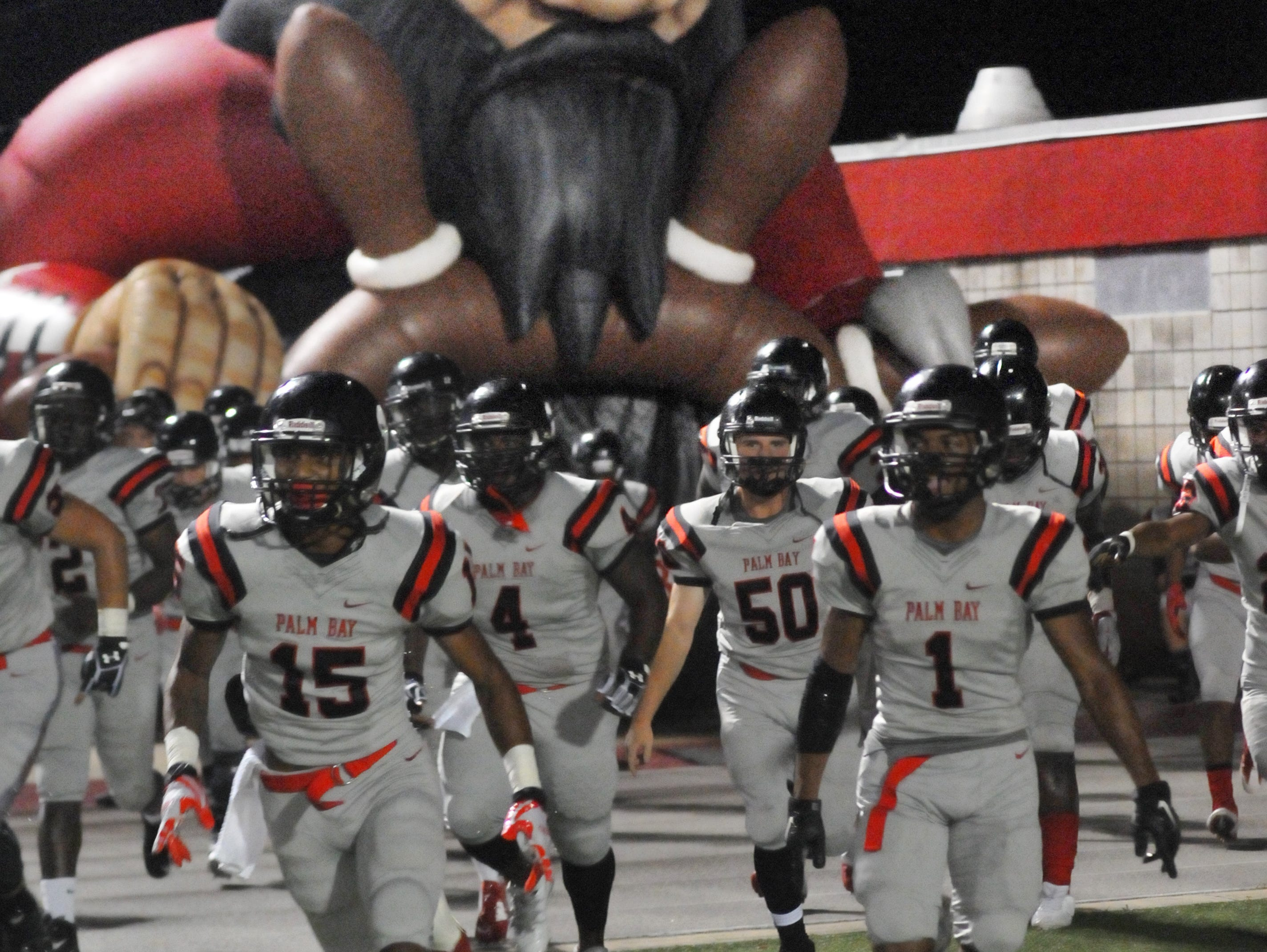 Palm Bay High's players take the field for Friday nights lightning delayed game with Titusville held at Palm Bay High football field .