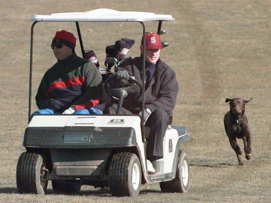 President Bill Clinton rides his golf cart with Tony