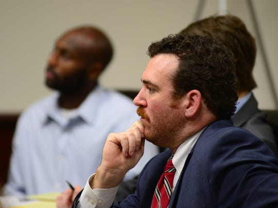 Public defender Jake Erwin, foreground, sits in court at the trial for Jonathan Donell Rhodes, who is sitting in the background and charged with murder in the 2012 deaths of Gary and Helen Wells.