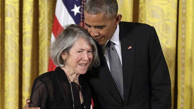 President Barack Obama embraces poet Louise Gluck before awarding her the 2015 National Humanities Medal during a ceremony in the East Room of the White House, in Washington.
