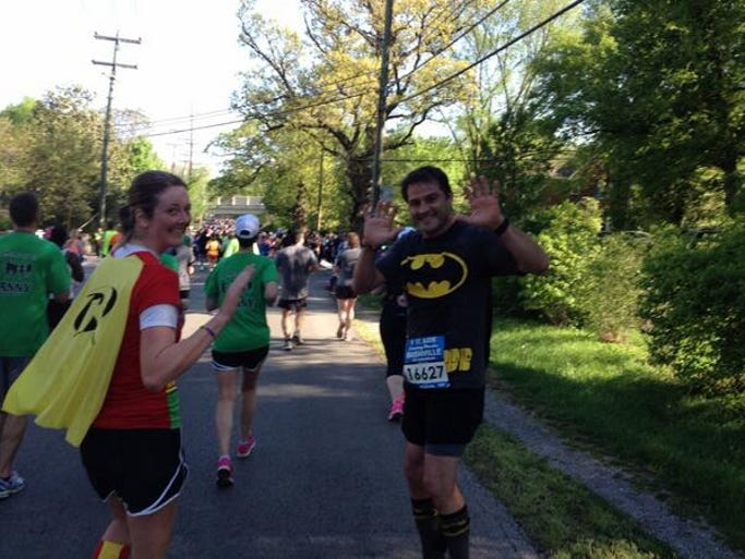 Participants dressed as Batman and Robin smile as they run the course in the 2014 Country Music Marathon.