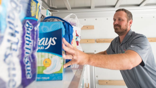 Nathan Gillum arranges the Hurricane Harvey relief donations in the back of a U-Haul truck that are being collected at Steiner's Speakeasy in Chillicothe, Ohio.