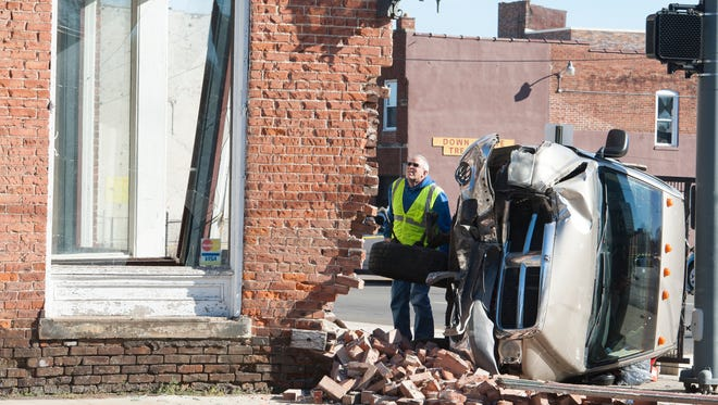 An official assesses building damage due to a mid-day accident at the corner of East Main Street and Mulberry in Chillicothe, Ohio.