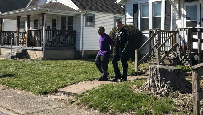 Chillicothe police officer Matthew Shipley escorts Greg Robinson, 51, from a house on Neal Avenue after multiple law enforcement agencies executed a search warrant in Friday's warrant sweep.