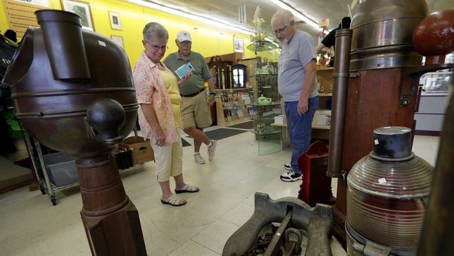 Archived photo of shoppers looking at an antique anchor for sale in BumblePuppy Sales in Grand Chute.