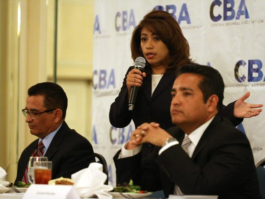 """Incumbent District Attorney Jaime Esparza, left, listens to challenger Yvonne Rosales answer one of five questions that were given to each candidate to respond to during the monthly luncheon of the Central Business Association on Wednesday afternoon at the Camino Real Hotel in Downtown El Paso. Leonard """"Lenny"""" Morales, the third candidate running for the office, also listens."""