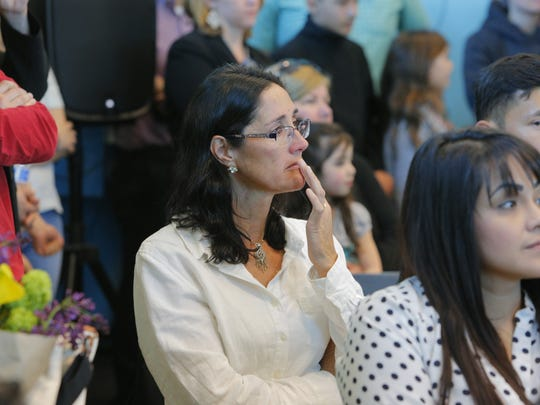 Delphine Houssin of France tears up as she listens to keynote speaker Congressman Jimmy Pannetta on Friday