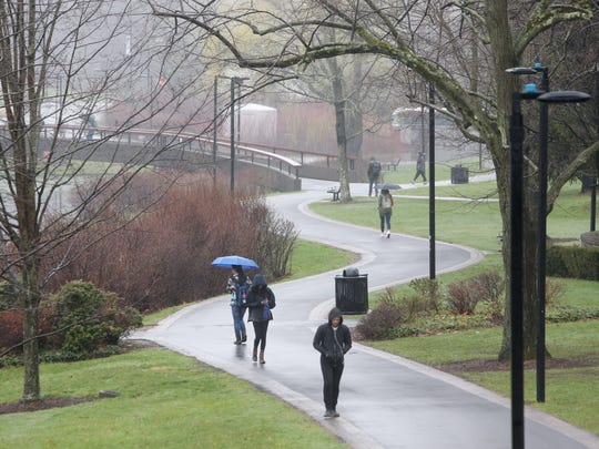 Students walk to and from class on a rainy day at SUNY New Paltz in April.