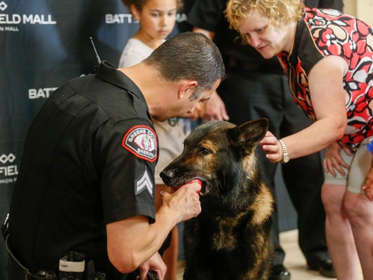 Cpl. James Craigmyle, left, and Laura Gwin pet Lor, a K-9 with the Greene County Sheriff's Office, during the Coffee with a Cop event at Battlefield Mall on Saturday, May 19, 2018.