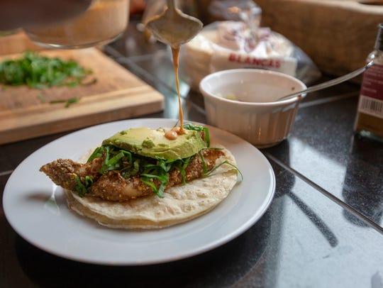 Craig Stodola tops his fish taco with a Mexican crema