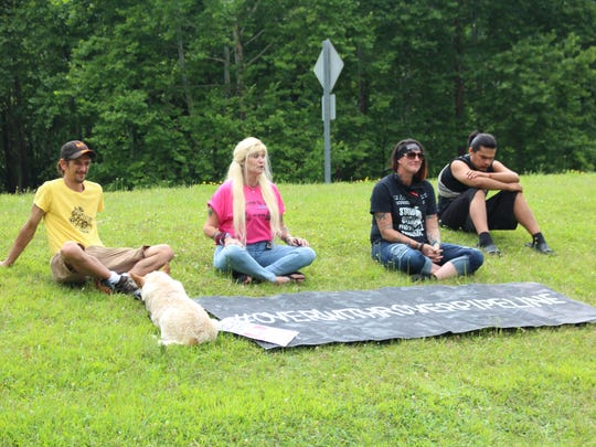 (From left to right) Flint, Michigan resident Matthew Borke and three Standing Rock protesters who asked not to be named but agreed to be photographed speak during a rally in Loudonville on Sunday, July 29, 2018. The rally protested the actions of Cabot Oil and Gas in the area.