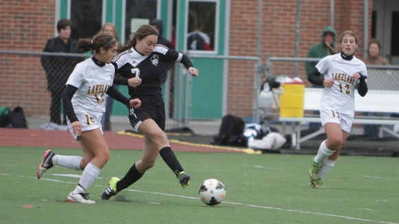 Rye's Lexi Brunner (7) passes the ball while being defended by Lakeland's Ashley Acevedo during a Section 1, Class A game at Lakeland High School on Saturday, October 24th, 2015. Lakeland won 1-0 in sudden death overtime.