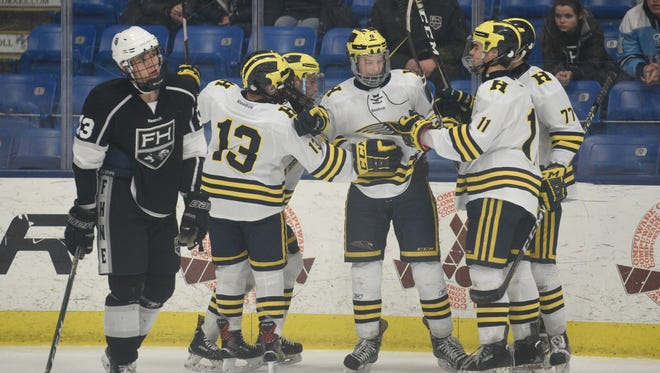 Hartland players celebrate a goal by Joey Larson (center) as Forest Hills' Cure Cumming skates past.