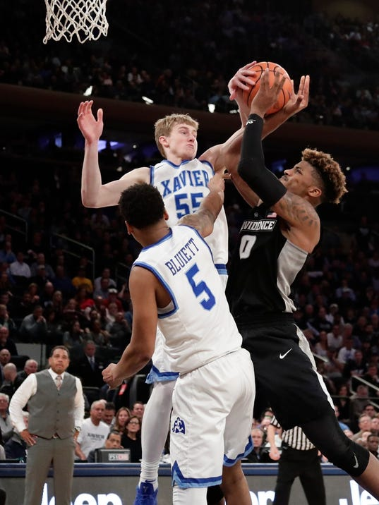Xavier's J.P. Macura (55) and Trevon Bluiett (5) defend Providence's Nate Watson (0) during overtime of an NCAA college basketball game in the Big East men's tournament semifinals Friday, March 9, 2018, in New York. (AP Photo/Frank Franklin II)