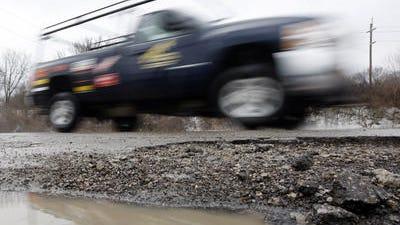 A truck drives by a large pothole on James Avenue, Covington.