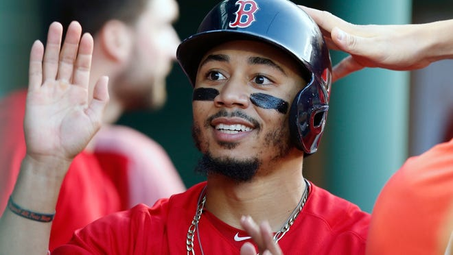 Boston Red Sox's Mookie Betts celebrates after scoring during a game against the Toronto Blue Jays in Boston on July 13, 2018.