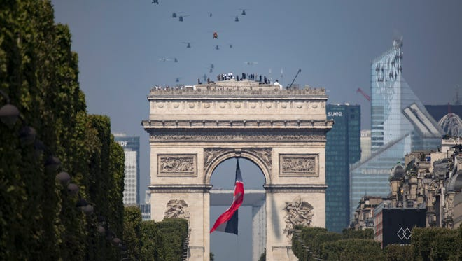 Helicopters fly over the Arc de Triomphe and the Champs Elysees during the annual Bastille Day military parade on the Champs Elysees avenue in Paris, France.