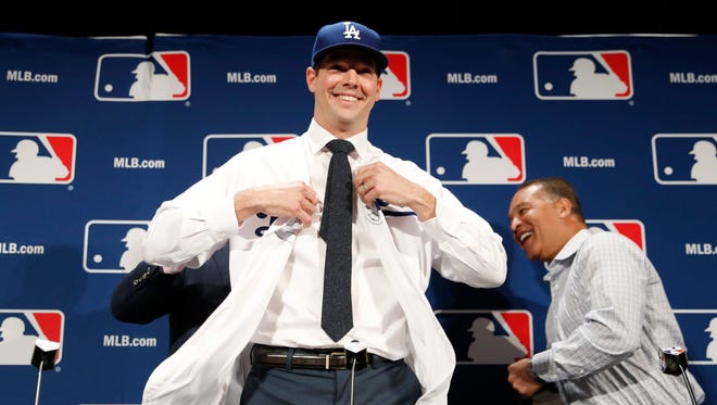 Los Angeles Dodgers pitcher Rich Hill puts on a jersey with manager Dave Roberts at right on Dec. 5, 2016, in Oxon Hill, Md.