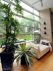 A chaise lounge affords a nice place to curl up and relaxnext to a wall of windows looking out onto the side yard. Large plants also help bring the outdoors in.