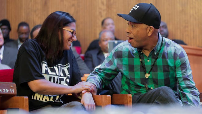 Russell Simmons reacts after noticing he's sitting next to Dr. Mona Hanna-Attisha of Hurley Medical Center in Flint who helped discover and force the state to realize the poisoning of residents from lead in the Flint water during a town hall meeting about the Flint water crisis on Monday February 1, 2016 at Flint Trinity Missionary Baptist Church.