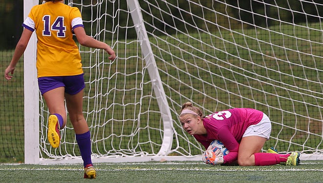 From left, Guerin Catholic's Elle Vuotto (14) watches as   Golden Eagles freshman goalkeeper Sarah Stagge (39) stops the ball during soccer regionals between Avon and Guerin Catholic at Carmel High School, Wednesday, October 12, 2016.