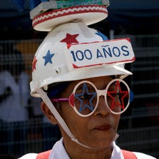 A woman dons a decorated hard hat Aug. 15 during the Panama Canal's centennial celebration in Panama City.  Panama ranks first in a new poll of global well-being.
