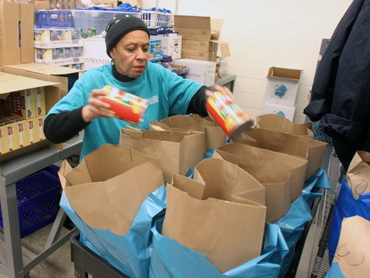 Volunteer Angela Pabon of New Brunswick helps in packing food bags that will be handed out to clients at the Franklin Food Bank.