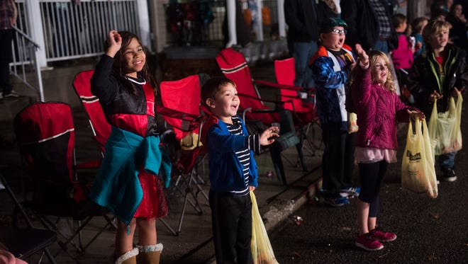 Kids smile and wave with bags of candy during the 75th annual Hanover Halloween Parade on Thursday.