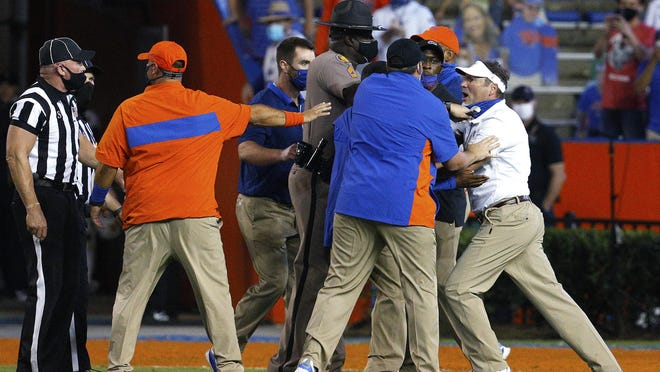 University of Florida head coach Dan Mullen, far right, is held back by coaches and law enforcement after a fight broke out at the end of the first half during a game against the Missouri Tigers at Ben Hill Griffin Stadium in Gainesville, Fla. Oct. 31, 2020.