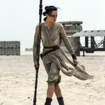 """Daisy Ridley, right, and John Boyega star in """"Star Wars: The Force Awakens,"""" directed by J.J. Abrams."""