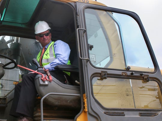County Mayor Jim Durrett sits in a wheeled excavator