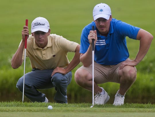 Drake Hull (left) and Bryan Smith line up their putts