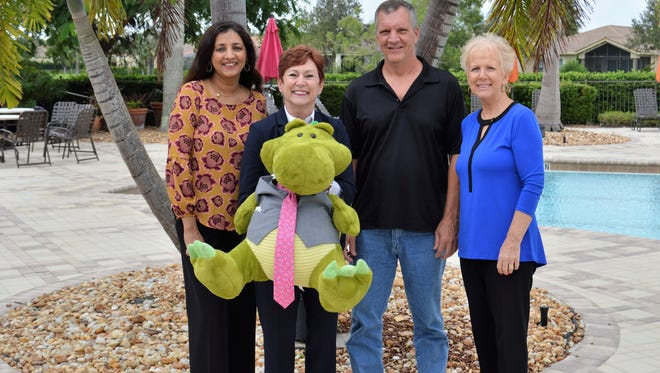 "From left, event committee members Naheed Shareef, Debbie Butler, with special mascot ""Gus"", Mike Henry, Guild President, and co-chair Beverley Sarlo, are pictured at the beautiful PGA Island Club getting ready for a fabulous event to benefit abused children."