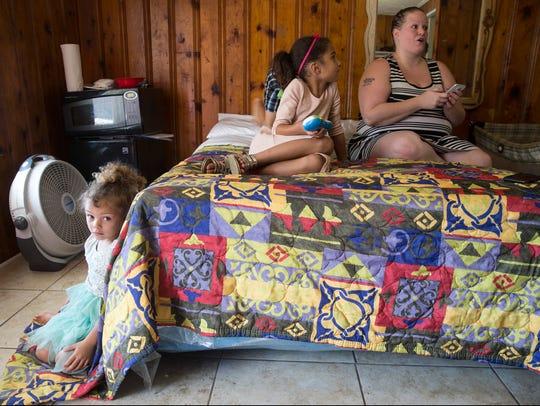 Jonniana, 4, sits on the floor of the small motel room