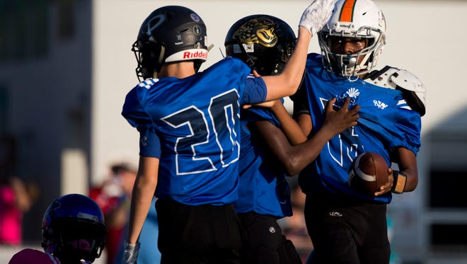 Team Tampa quarterback Charles Coney, right, is congratulated by teammates after scoring against Team Dade during the FBU Sixth Grade National Championship game at Gulf Coast High School Thursday, Dec. 21, 2017 in Naples. Tampa would go on to win 32-0.