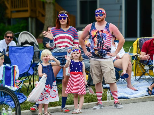 Karina Walters, Andrew Chiovaro, Lakelei Walters, then 4, (left) and Lexie Steffy, then 4, (right) wave at the firemen as they go by on Monday, July 4, 2016, during the Urbandale Independence Day Parade.