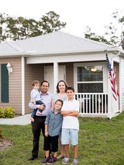 """Darrell and Tiffany Evans with their children Ronin, 1, from left; Sevrin, 8; and Mikael, 12, outside their home in the Legacy Lakes community Tuesday, April 11, 2017, in North Naples. """"We couldn't afford the apartments anymore once I got pregnant with my youngest child (Ronin),"""" Tiffany said. """"I know that it's safe here. It's very family-oriented. It's a tight community."""" The Evans family went through a extensive process to be accepted and once accepted had to volunteer hundreds of hours building their own home. """"This place was a long shot,"""" said Darrell. """"A lot of these people I was working on a home with. I can trust people here."""""""
