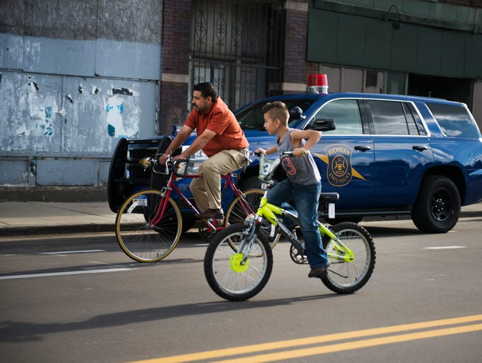 A family rides down Vernor Avenue during Open Streets
