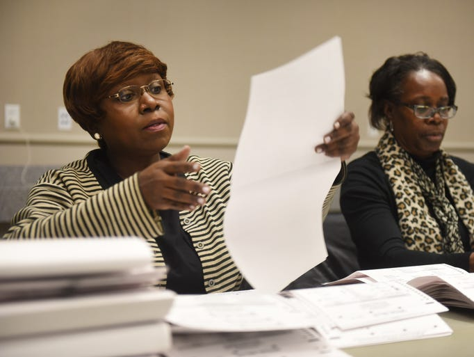 M.V. Ward, left, of Detroit, is surrounded by ballots