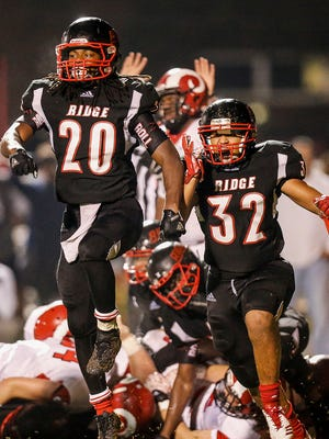 PRP players Bryson Washington (20) and Korei Shephard (32) run off the field in celebration after stopping Manual on fourth and goal at the one-yard-line as time expired. Friday, Oct. 13, 2017.
