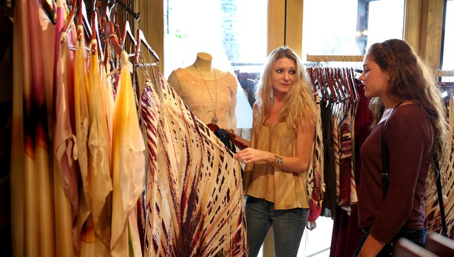 Rochelle LaBrie, left, a sales associate, helps Samantha Simpson with her shopping at Ramona LaRue by Arianna on March 25, 2014 in Fort Lauderdale, Fla.