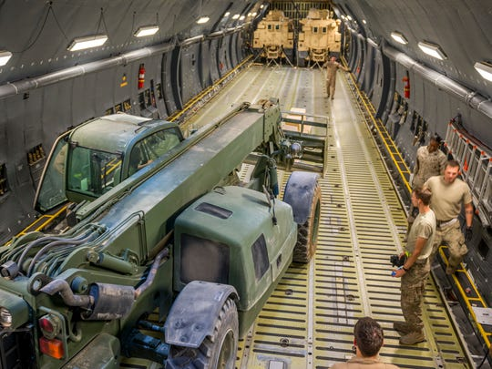 Airmen from the 9th Airlift Squadron and 455th Expeditionary Aerial Port Squadron with Marines from the Marine Expeditionary Brigade prepare to load vehicles into a C-5M Super Galaxy Oct. 6 at Camp Bastion, Afghanistan. Airmen and Marines loaded more than 266,000 pounds of cargo onto the C-5M as part of retrograde operations in Afghanistan.