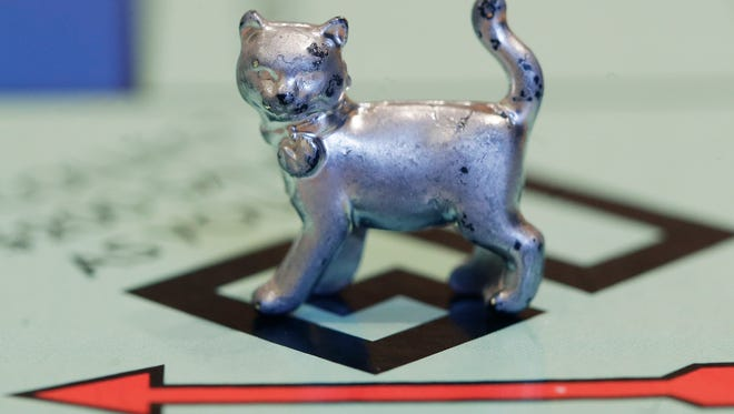 The newest Monopoly token, a cat, rests on the game board at Hasbro Inc. headquarters, in Pawtucket, R.I. Hasbro Inc. (HAS) on Monday, April 23, 2018, reported a first-quarter loss of $112.5 million, after reporting a profit in the same period a year earlier.