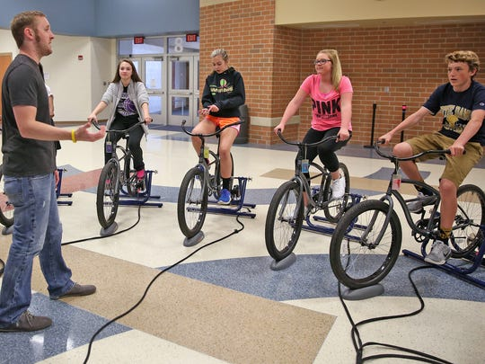 Nine13sports' Chris Harris (left) explains what to do before Avon Middle School North students start a cycling session on stationary bikes.