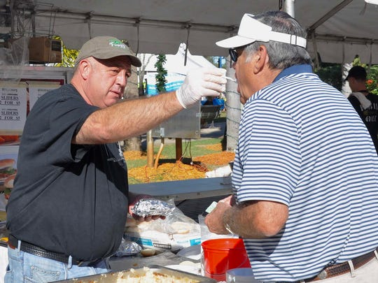 Campbell Fitzgerald gives Don McLeod a sample of Bubble and Squeak during Taste of Bonita Nov. 20. Fitzgerald's Pub was one of 25 participating restaurants.