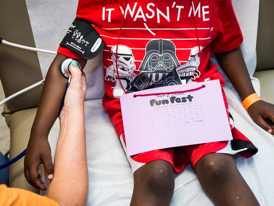 A child receives a school physical at Open Door Health Services in this file photo.