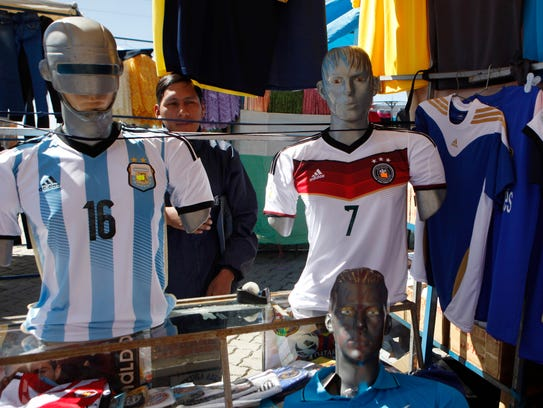 A street vendor displays two mannequins with the jerseys of Argentina's Marcos Rojo, left, and Germany's Bastian Schweinsteiger at a street market in El Alto, Bolivia, Thursday, July 10, 2014. As Germany and Argentina prepare to dispute the 2014 FIFA Soccer World Cup title, on Sunday 13, the stand owner says he sells more Germany jerseys over all. (AP Photo/Juan Karita)